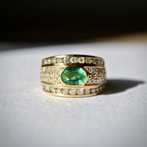 An Oval Emerald and Diamond Band RIng