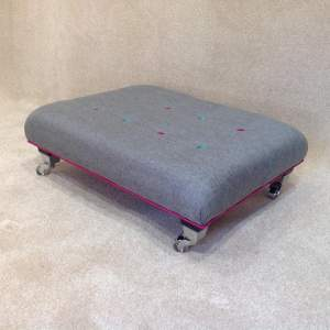 1.0010 - Small dark grey wool footstool with pink & blue buttons.JPG