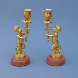 A Pair of Ormolu Cherub Candlesticks