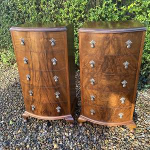 A Pair of Walnut Bow Front Chests of Drawers