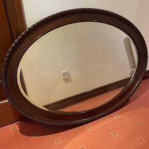 A Large Oval Mahogany Wall Mirror