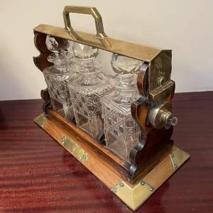 An Oak Three Decanter Tantalus with Brass Fittings
